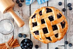 Homemade blueberry pie, top view baking scene over a white wood background stock photos
