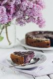 Homemade blueberry pie on a white wooden table next to a vase of. Lilacs. Gentle toning. Selective focus stock photography
