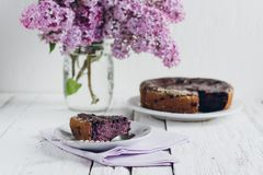Homemade blueberry pie on a white wooden table next to a vase of. Lilacs. Gentle toning. Selective focus royalty free stock photo