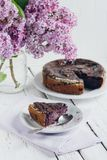 Homemade blueberry pie on a white wooden table next to a vase of. Lilacs. Gentle toning. Selective focus royalty free stock photography