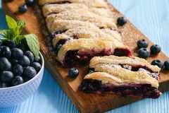 Homemade blueberry puff pastry braid, on blue wooden background. Royalty Free Stock Photos