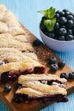 Homemade blueberry puff pastry braid, on blue wooden background. Royalty Free Stock Images