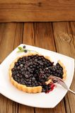 Homemade blueberry tart cut in square white plate with fork and Royalty Free Stock Image