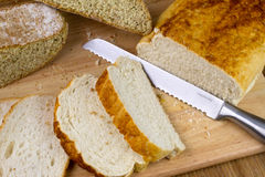 Homemade bread. A loaf of homemade bread on a breadboard with a breadknife Royalty Free Stock Photos