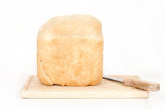 Homemade Bread on Breadboard Flat Front View. A flat front studio view of a loaf of homemade bread on a wooden breadboard with a bread knife Royalty Free Stock Photo