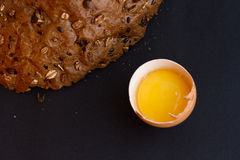 Homemade bread with cereals and fresh egg on a black background. For sample texte on it Royalty Free Stock Photos