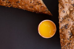 Homemade bread with cereals and fresh egg on a black background. For sample texte on it Royalty Free Stock Photography