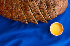 Homemade bread with cereals and fresh egg on a blue background. For sample texte on it Royalty Free Stock Photo