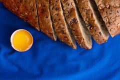 Homemade bread with cereals and fresh egg on a blue background. For sample texte on it Royalty Free Stock Photography