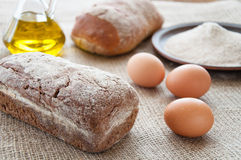 Homemade bread ciabatta on the table. Olive oil, eggs Stock Photos