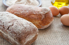 Homemade bread ciabatta on the table. Olive oil, eggs Stock Photos