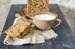 Homemade bread on cutting board with cup of milk Stock Photos