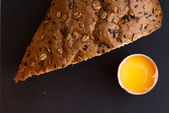 Homemade bread with fresh egg and cereals. On a black background for sample texte on it Royalty Free Stock Photos