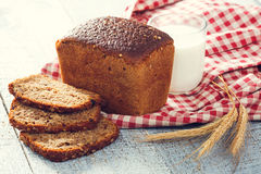 Homemade bread and milk with spikelets of wheat on a cloth on a  boards Royalty Free Stock Photo