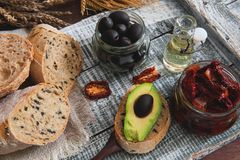 Homemade bread with olives with sun-dried tomatoes, avocado and olive oil Stock Images