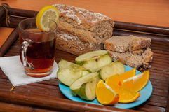 Homemade bread and other food. Homemade buckweat bread, tea with lemon, apples and oranges on tray royalty free stock images