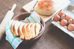 Homemade Bread Ready To Eat With Loaf Of Bread, eggs and bakery tools on wood Royalty Free Stock Photography