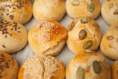 The homemade bread rolls with sesame seeds hamburger with sesame, pumpkin, flax, sunflower seeds on the tray, concept of burger royalty free stock images
