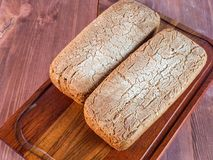 Loaf of home baked bread on wooden cutting board Stock Photos
