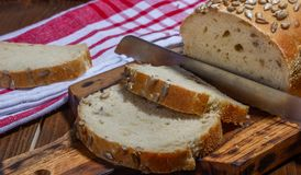 Homemade bread with sunflower seeds, cutting board and knife. royalty free stock images