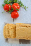 Homemade bread and tomatoes. On the table is the home of sliced cheese bread tomatoes basil royalty free stock photos