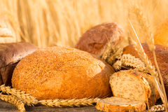 Homemade bread and wheat on the wooden table Stock Photos