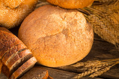 Homemade bread and wheat on the wooden table Stock Photography