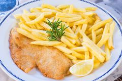 Homemade breaded chicken breast or Milanese chicken cutlet with tasty and crispy french fries Stock Photos