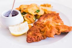 A Homemade Breaded German Weiner Schnitzel with cooked Potatoes royalty free stock image