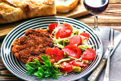 Homemade Breaded German Weiner Schnitzel and fresh vegetable spring salad with tomato, green olives, cabbage and parsley Royalty Free Stock Images