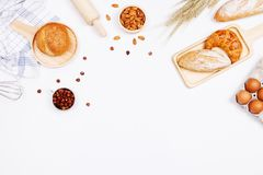 Homemade breads or bun, croissant and bakery ingredients, flour,. Almond nuts, hazelnuts, eggs on white background, Bakery background frame, Cooking breakfast stock image