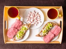 Homemade breakfast: bread with ham, onions, radish. And tea, prepared for a couple, top Stock Photo