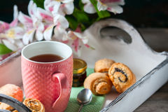 Homemade breakfast: rolls and cup of tea on vintage serving tray. Royalty Free Stock Images