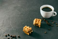 Homemade breakfast, stone black table. Viennese waffles, a cup of coffee, scattered coffee beans, vertical view, copy space royalty free stock photography