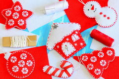 Homemade bright Christmas decorations. Snowman, house, ball, tree, star, candy ornaments made of felt. Thread, needle, ribbon, Royalty Free Stock Image