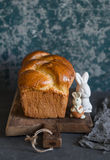 Homemade brioche and ceramic easter rabbits on a rustic cutting board. Front view. Royalty Free Stock Images