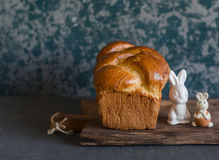 Homemade brioche and ceramic easter rabbits on a rustic cutting board. Front view. Royalty Free Stock Photo