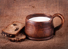 Homemade brown clay cup with milk and  bread. On jute background Royalty Free Stock Image