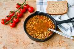 Homemade Brown Lentil soup. With Carrots Onions and Tomatos and cheese soldiers and bread on wooden rustic backgrouns royalty free stock photos