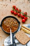 Homemade Brown Lentil soup. With Carrots Onions and Tomatos and cheese soldiers and bread on wooden rustic backgrouns royalty free stock photography