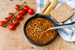 Homemade Brown Lentil soup. With Carrots Onions and Tomatos and cheese soldiers and bread on wooden rustic backgrouns royalty free stock images