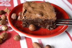 Homemade brownie. Chocolate cake with nuts and almonds, on red saucer with fork, with whole walnuts and almonds, on cloth in white - red stripes; cake for Stock Photo