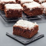 Homemade brownie with coconut flakes, swedish dessert Karleksmums, cut in square servings, on stone plate and cooling rack, square royalty free stock photo