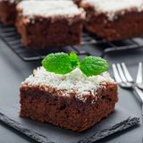 Homemade brownie with coconut flakes, swedish dessert Karleksmums, cut in square servings, on stone plate and cooling rack, square stock images