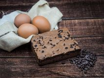 Homemade Brownie and ingredients with chocolate chip, egg on wood background stock photography