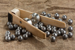 Homemade bullet mold and ball-shaped bullets on burlap Royalty Free Stock Photo