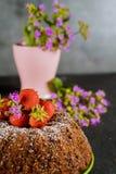 Homemade bundt cake with fresh strawberries and flowers on black table. Bundt cake with fresh strawberries and flowers on background, homemade, baked, fruit stock photography