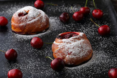 Homemade buns with cherry on black background Stock Photo