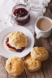Homemade buns with jam and tea with milk close-up. Vertical Royalty Free Stock Photo