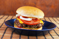 Homemade burger. With cheese on blue dish Stock Photography